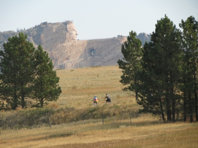 Bicyclist cruising by the Crazy Horse mountain carving. It's a work in progress that all trail users can see. Photo by Brooke Smith.