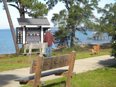 Trail walker and dog stopped at interpretive sign. Photo by Sherry Sullivan.