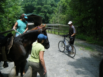 Horseback riders and cyclist visit at a covered bridge. Photo by Kari Kirby.