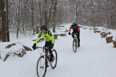 Mountain bikers in the snow on Turkey Mountain.