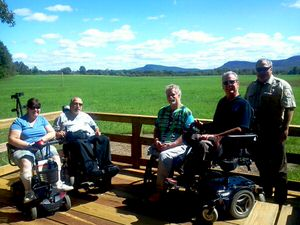 Visitors on the trail pose with the Refuge manager at the grassland overlook, which provides views of the Mount Holyoke Range, one of two east/west mountain ranges in the Northeast.